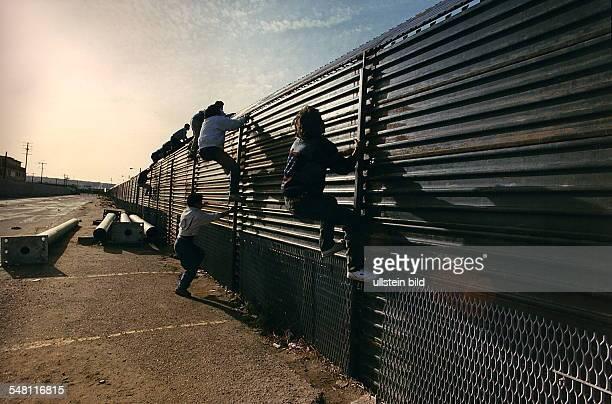 Illegale Einwanderer aus Mexiko versuchen die amerikanischmexikanische Grenze zu überwinden