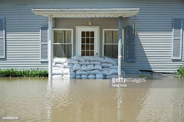 USA, Illinois, Facade of flooded house with wall made of bags with sand