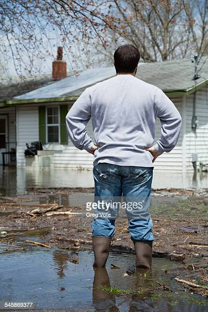 USA, Illinois, Man standing in front of flooded house