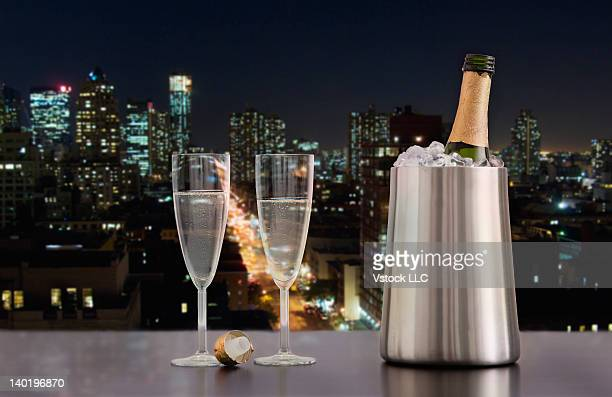 USA, Illinois, Metamora, Champagne flutes and bottle in ice bucket with downtown skyline in background