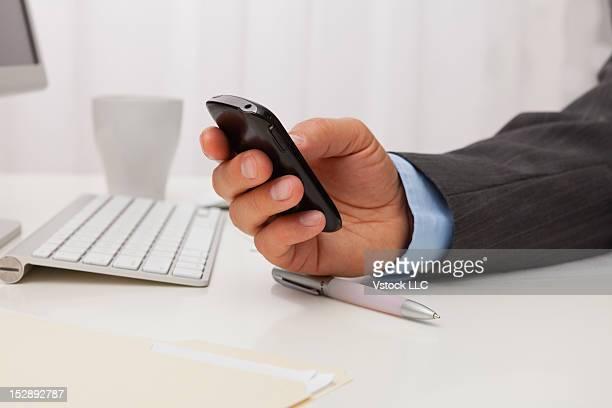 USA, Illinois, Metamora, close-up of business man text messaging