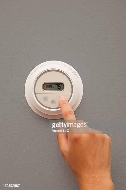 USA, Illinois, Metamora, close-up of woman adjusting thermostat