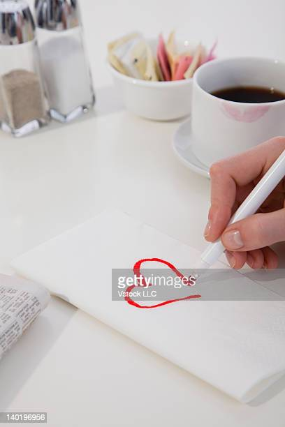 USA, Illinois, Metamora, Close-up of woman's hand drawing heart on napkin