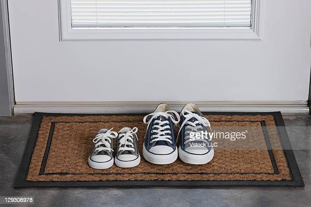 USA, Illinois, Metamora, Father's and daughter's shoes on door mat