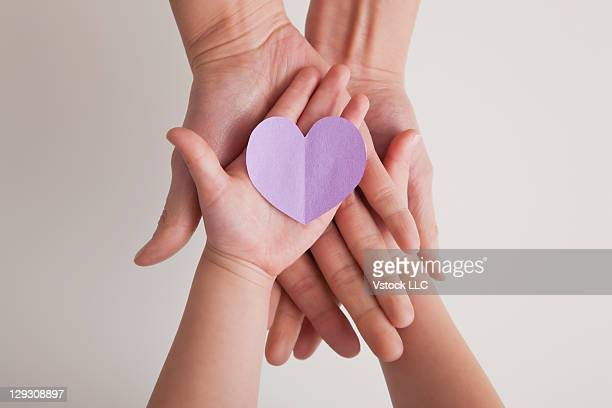USA, Illinois, Metamora, Hands of mother and daughter (4-5) holding paper heart