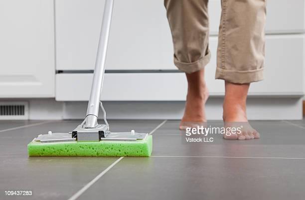 USA, Illinois, Metamora, Housewife mopping kitchen floor