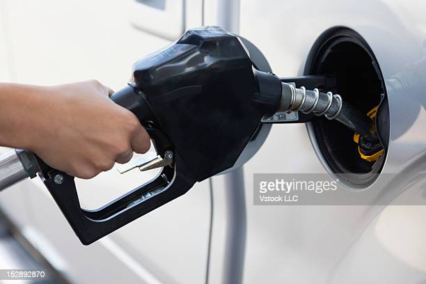 USA, Illinois, Metamora, woman holding fuel pump