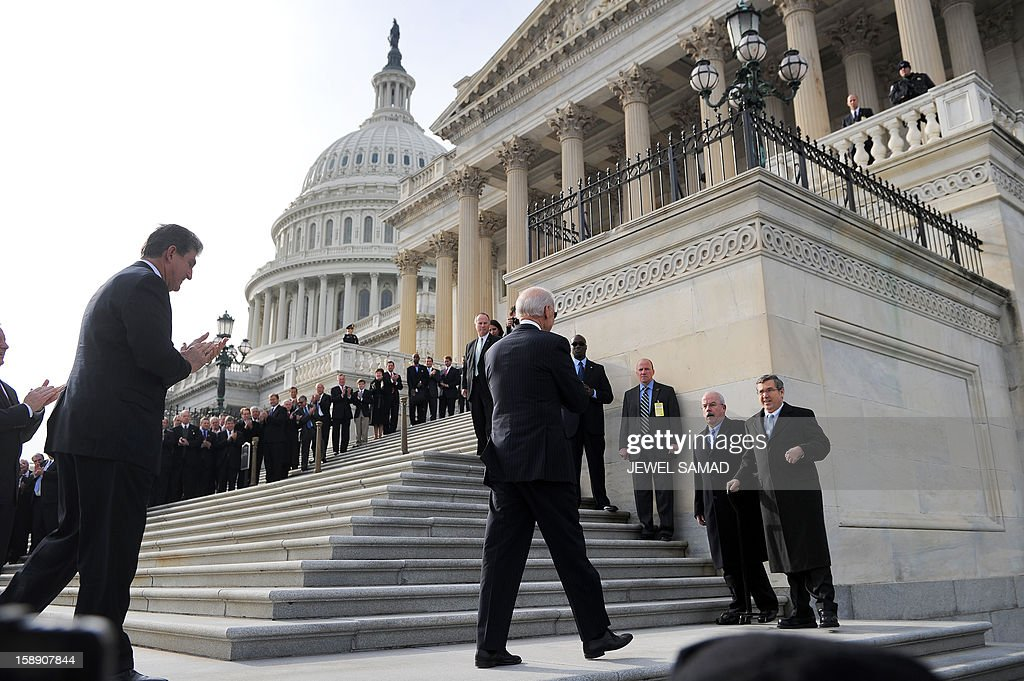 Illinois Senator Mark Kirk (R) is welcomed by US Vice President Joe Biden (C) and his colleagues upon his return to the Senate on January 3, 2013 after suffering a stroke last January. Krik was welcomed by his colleagues on the step of the Senate a year after a stroke affected the right side of his brain. Kirk spent a year relearning how to walk in intensive physical therapy. The 113th Congress convenes Thursday fresh from the year-end fiscal cliff fiasco, but lawmakers will ring in 2013 casting a wary eye towards the even tougher budget battles that lie ahead. AFP PHOTO/Jewel Samad