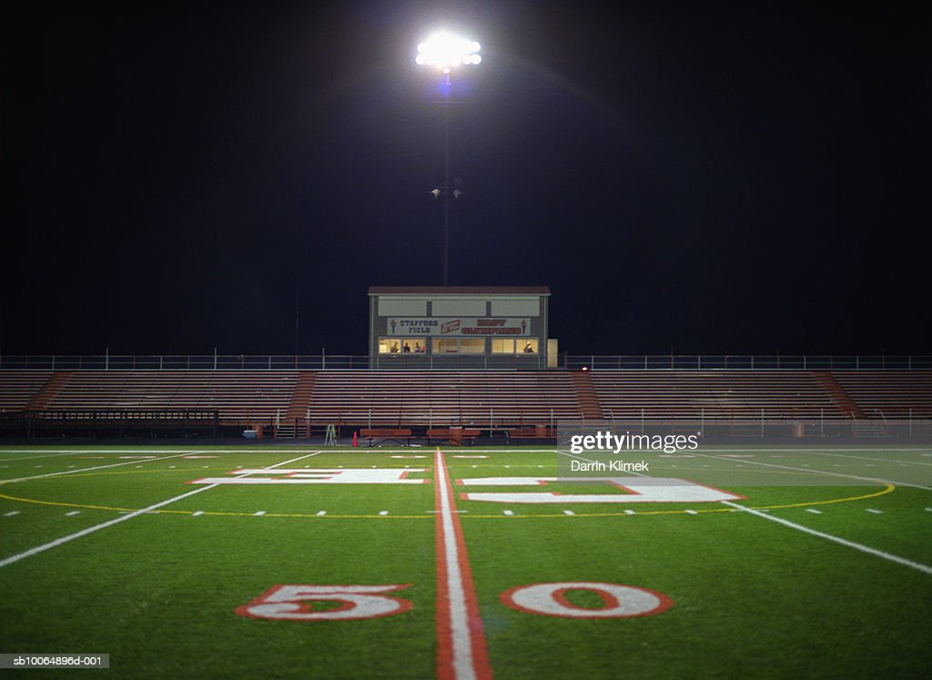 Illuminated American football field at night : Stock Photo