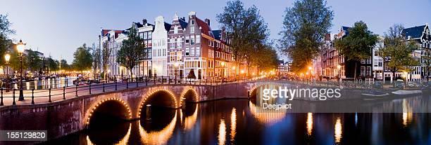 Beleuchtete Amsterdam Kanal-Brücken in der Nacht Holland