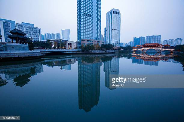Illuminated Anshun Bridge with reflection in a modern city