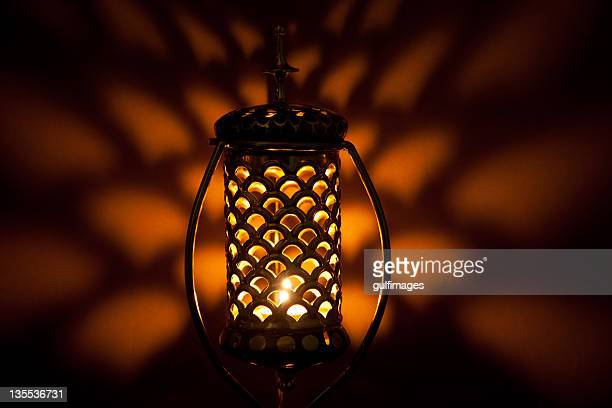Illuminated Arabic style bronze metallic lantern with lattice pattern