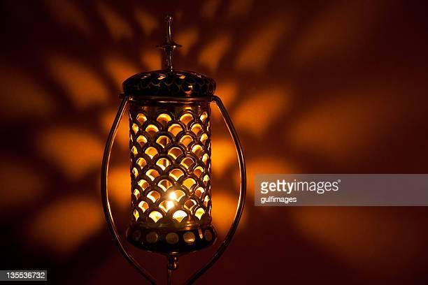 Illuminated Arabic style bronze metallic lantern with lattice pattern
