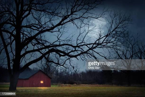 Illuminated barn in rural landscape
