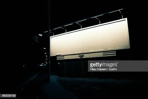 Illuminated Billboard By Street At Night