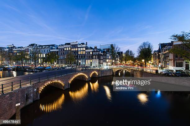 Illuminated bridge over canal in Amsterdam Netherlands at dusk with light trails