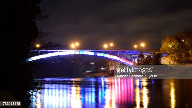 Illuminated Bridge Over River In City At Night