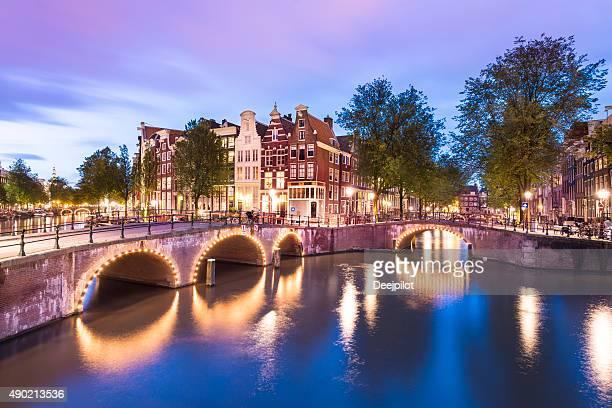 Ponts illuminés et maisons au bord du Canal à Amsterdam, Pays-Bas
