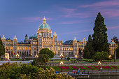 Dusk view of the Parliament Building in Victoria, BC, Canada. The Path alongside the Harbour and the word Welcome Written in Flowers are in Foreground