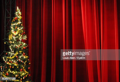 Illuminated Christmas Tree In Front Of Stage Curtains Stock Photo ...