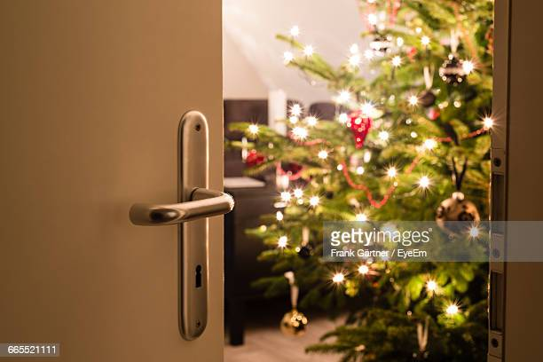 Illuminated Christmas Tree Seen Through Ajar Door