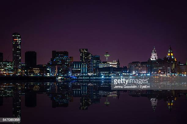 Illuminated City Skyline By River Against Sky At Night