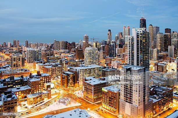 Illuminated Cityscape During Winter Against Sky