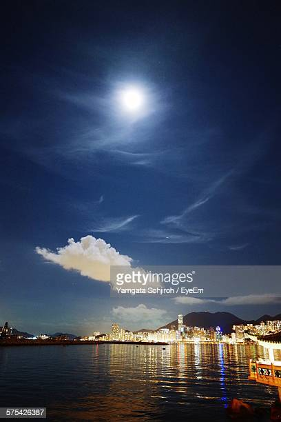 Illuminated Cityscape In Front Of River Against Moon In Blue Sky At Night