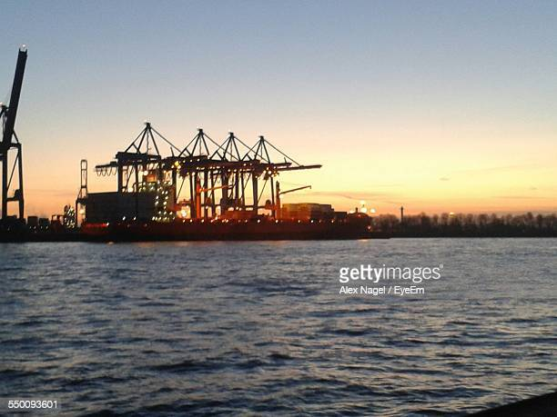 Illuminated Container Ship In Sea Against Clear Sky During Sunset At Harbor