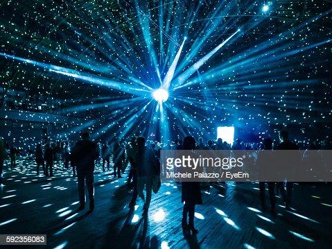 Illuminated Disco Ball Over Silhouette People In Nightclub