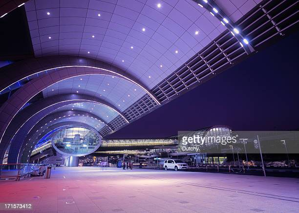 Illuminated Dubai International Airport at dusk, UAE
