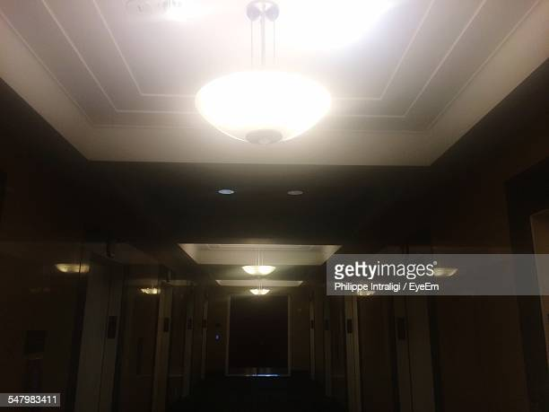Illuminated Electric Lamps Hanging On Ceiling In Hotel