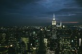 Illuminated Empire State Building Amidst Modern Towers At Night