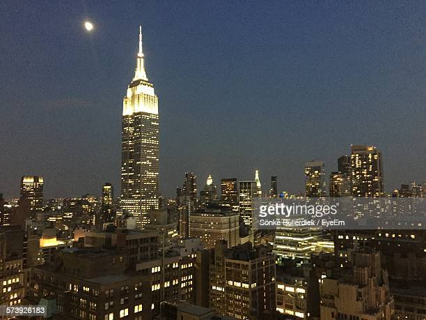 Illuminated Empire State Building And Cityscape Against Sky