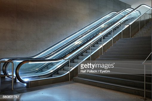 Illuminated Escalator By Steps In Building