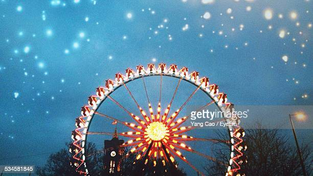 Illuminated Ferris Wheel Against Star Field In Sky At Night