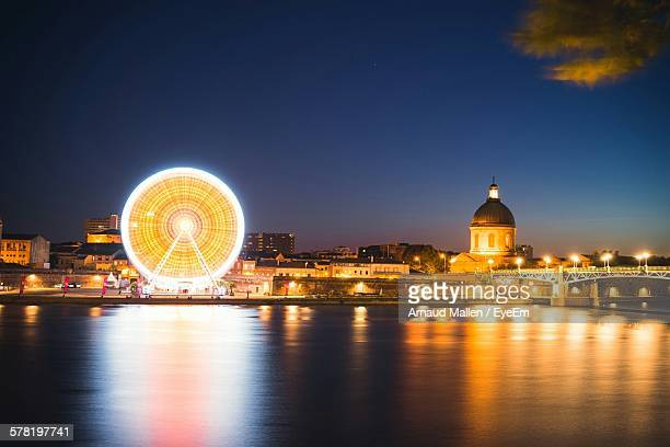 Illuminated Ferris Wheel And Hospital De La Grave By River Against Sky At Dusk