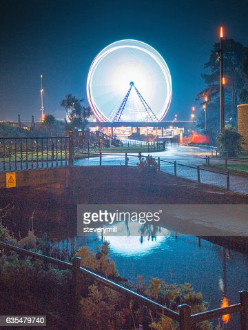Illuminated Ferris Wheel reflected in a steam : Stock Photo