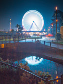 A moon like reflection of an illuminated Big Ferris Wheel in a stream in the Bournemouth Park Gardens.