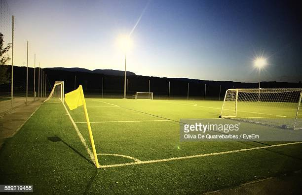 Illuminated Floodlight On Soccer Field Against Clear Sky At Dusk