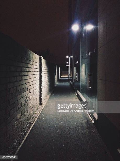 Illuminated Footpath Amidst Wall And Building At Night