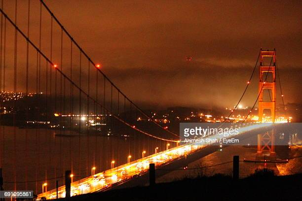 Illuminated Golden Gate Bridge Against Cloudy Sky At Night