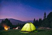Illuminated  green  tent under stars at night  forest , Carpathian ,Ukraine