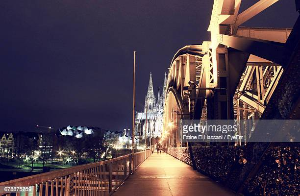 Illuminated Hohenzollern Bridge Against Cologne Cathedral At Night