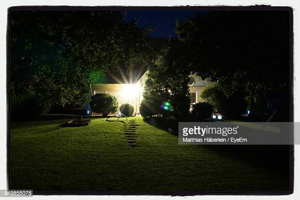 Illuminated House With Lawn At Night