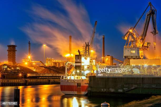 Beleuchtete industrielle Anlage am Fluss bei Nacht, Amsterdam, Niederlande