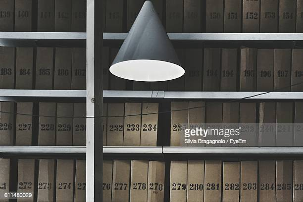 Illuminated Lamp Against Books In Library