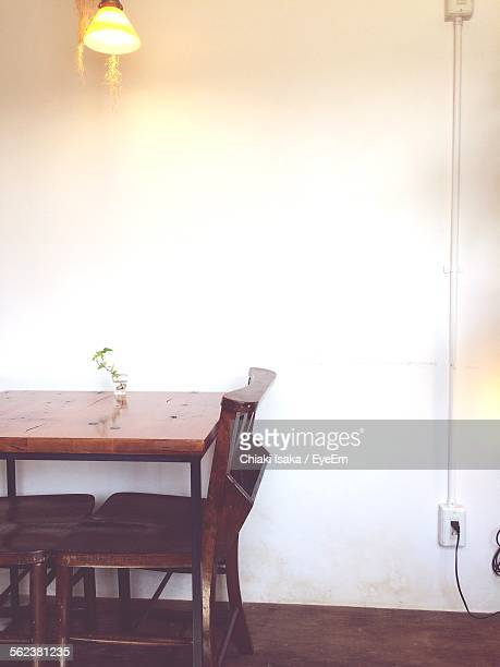 Illuminated Lamp Over Empty Chair And Table By Wall At Cafe