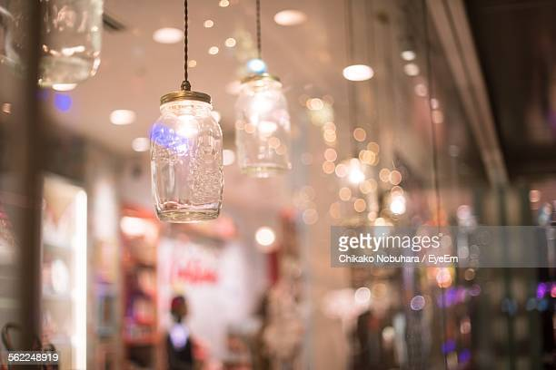 Illuminated Lamps Hanging Outside Shop In City At Night