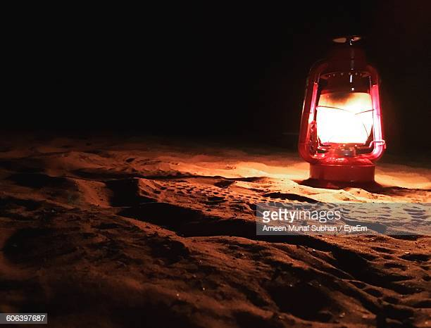 Illuminated Lantern On Sandy Beach At Night